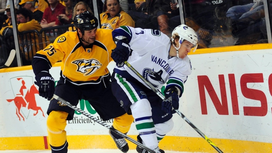 Nashville Predators' Hal Gill (75) and Vancouver Canucks' David Booth (7) tries to control the puck in the first period of an NHL hockey game on Friday, Feb. 22, 2013, in Nashville, Tenn. (AP Photo/Mike Strasinger)