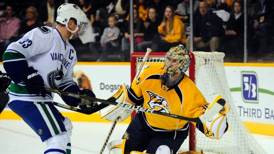 Nashville Predators' Pekka Rinne, of Finland, makes a glove save in front of Vancouver Canucks' Henrik Sedin (33), of Sweden, in the first period of an NHL hockey game on Friday, Feb. 22, 2013, in Nashville, Tenn. (AP Photo/Mike Strasinger)