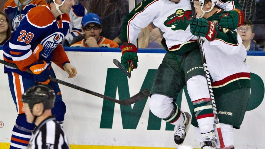 Minnesota Wild's Matt Cullen (7) and Jonas Brodin celebrate Cullen's goal as Edmonton Oilers' Eric Belanger (20) skates past during the second period of an NHL hockey game in Edmonton, Alberta, on Thursday, Feb. 21, 2013. (AP Photo/The Canadian Press, Jason Franson)
