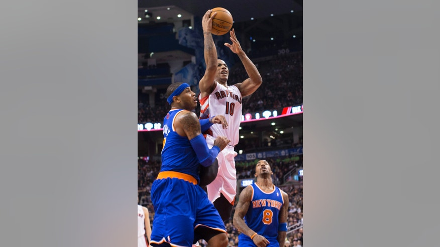 Toronto Raptors' DeMar DeRozan shoots above New York Knicks' Carmelo Anthony, left, and J.R. Smith during the first half of an NBA basketball game in Toronto on Friday, Feb. 22, 2013. (AP Photo/The Canadian Press, Chris Young)