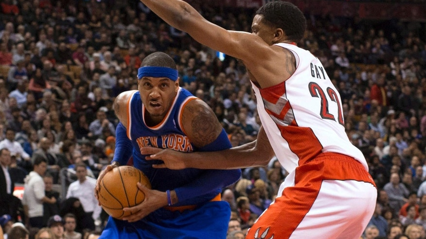 New York Knicks' Carmelo Anthony, left, drives on Toronto Raptors' Rudy Gay during the first half of an NBA basketball game in Toronto on Friday, Feb. 22 , 2013. (AP Photo/The Canadian Press, Chris Young)