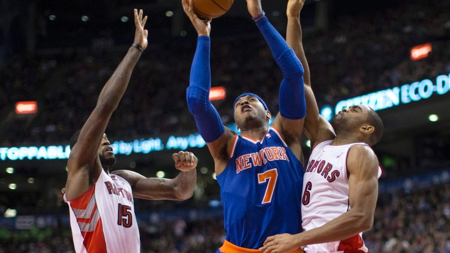New York Knicks' Carmello Anthony shoots between Toronto Raptors' Amir Johnson, left, and Alan Anderson during the second half of an NBA basketball game in Toronto on Friday, Feb. 22, 2013. (AP Photo/The Canadian Press, Chris Young)