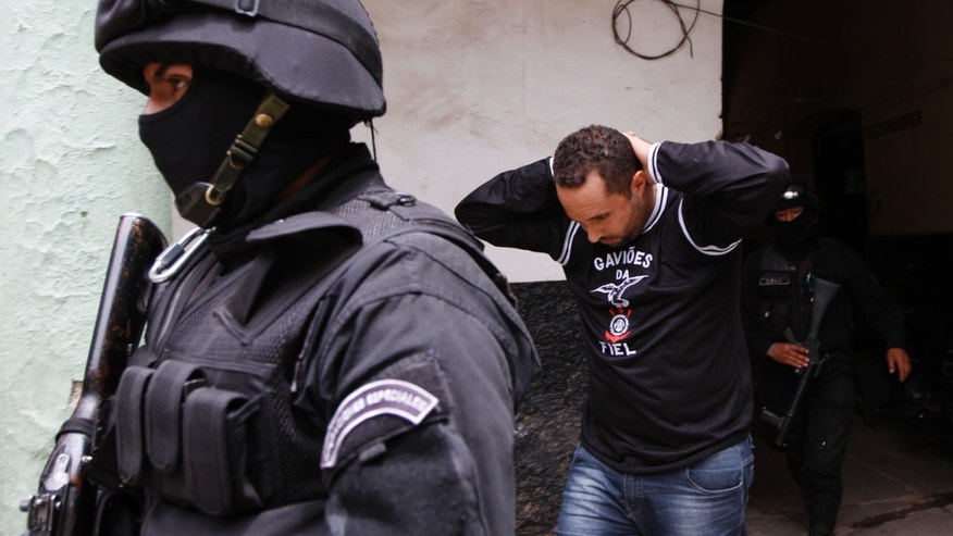 A man identified by police as a Corinthians soccer fan, right, is escorted by police to the police station's offices in Oruro, Bolivia, Thursday, Feb. 21, 2013. Twelve Corinthian soccer fans were arrested on suspicion of having caused the death of a 14-year-old San Jose soccer fan by launching an explosive device during a Copa Libertadores game between San Jose and Corinthians on Wednesday in the Bolivian city of Oruro, according to police. (AP Photo/Juan Karita)