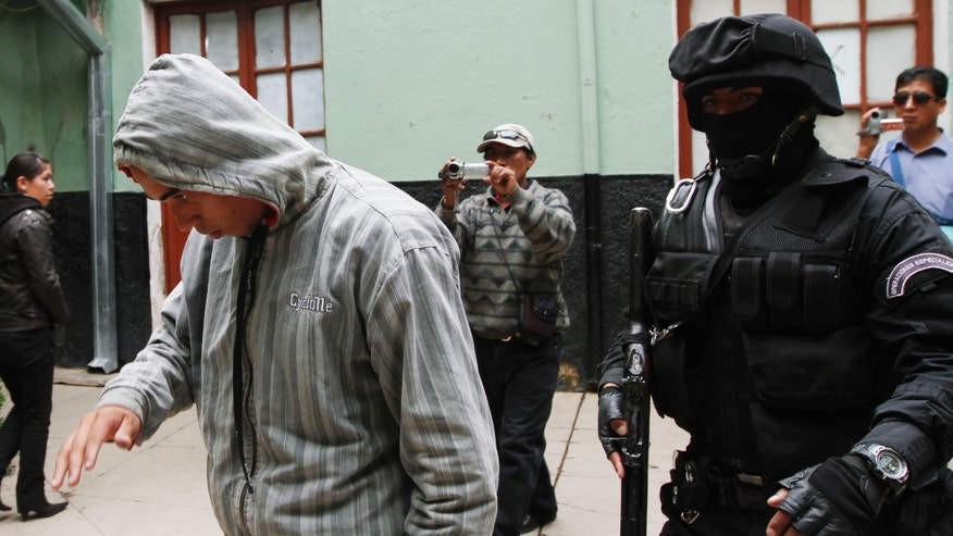 A man identified by police as a Corinthians soccer fan, left, is escorted by police to the police station's offices in Oruro, Bolivia, Thursday, Feb. 21, 2013. Twelve Corinthian soccer fans were arrested on suspicion of having caused the death of a 14-year-old San Jose soccer fan by launching an explosive device during a Copa Libertadores game between San Jose and Corinthians on Wednesday in the Bolivian city of Oruro, according to police. (AP Photo/Juan Karita)