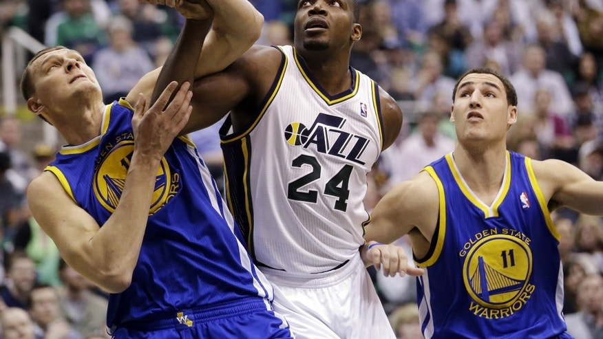 FILE - In this Feb. 19, 2013, file photo, Utah Jazz forward Paul Millsap (24) battles with Golden State Warriors' Andris Biedrins (15) and Klay Thompson (11) under the boards in the second half of an NBA basketball game in Salt Lake City. The trade deadline passed Thursday, Feb. 21, without the Jazz dealing either Millsap or center Al Jefferson, leaving intact a team that is seven games above .500 entering the stretch run toward the playoffs. (AP Photo/Rick Bowmer, File)
