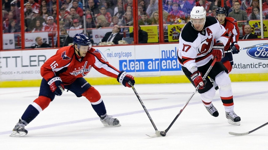 New Jersey Devils right wing Ilya Kovalchuk (17), from Russia, skates with the puck as Washington Capitals right wing Joey Crabb (15) reaches for it during the second period of an NHL hockey game Saturday, Feb. 23, 2013, in Washington. (AP Photo/Alex Brandon)