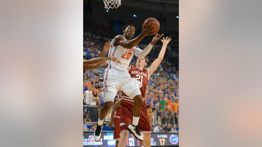 Florida guard Michael Frazier II (20) tries to get to the basket with Arkansas forward Hunter Mickelson (21) defending during the first half of an NCAA college basketball game in Gainesville, Fla., Saturday, Feb. 23, 2013. (AP Photo/Phil Sandlin)