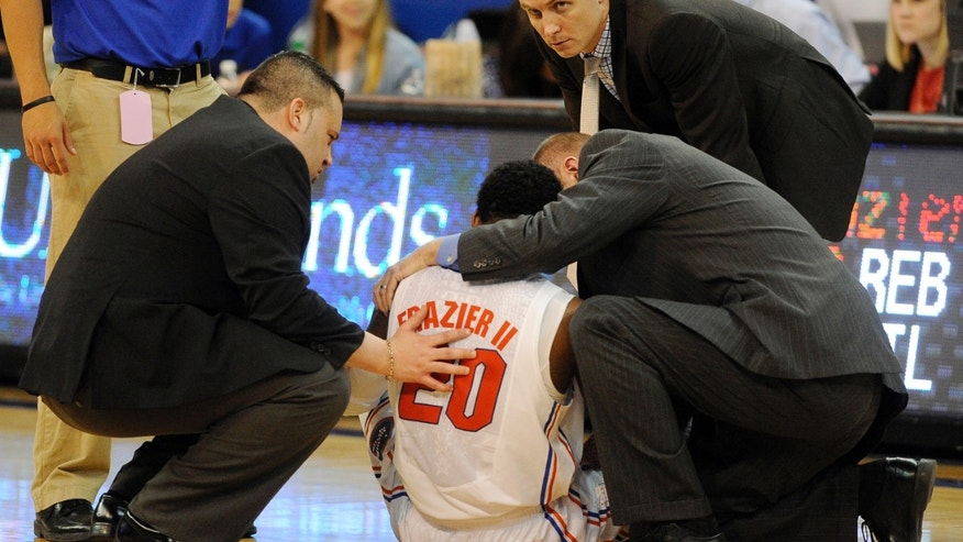 Dr. Kevin Farmer, left, and Florida medical staff care for Michael Frazier II (20) after he was injured  against Arkansas in the second half of an NCAA college basketball game in Gainesville, Fla., Saturday, Feb. 23, 2013. Florida won 71-54. (AP Photo/Phil Sandlin)