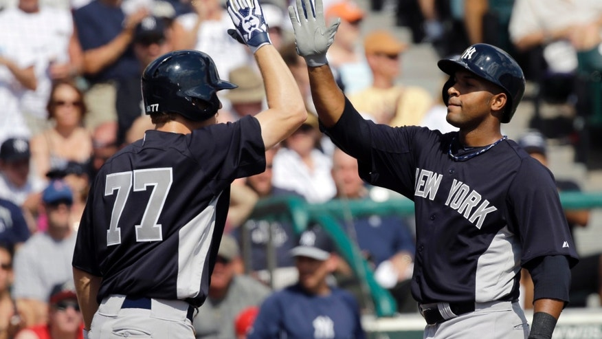 New York Yankees' Zoilo Almonte, right, is congratulated by Corban Joseph (77) after hitting a two-run home run against the Atlanta Braves during an exhibition spring training baseball game, Saturday, Feb. 23, 2013, in Kissimmee, Fla. Melky Mesa scored on Almonte's homer. (AP Photo/David J. Phillip)