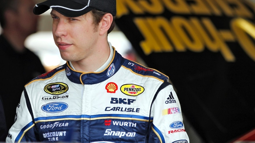 Brad Keselowski looks out of the garage while crew members work on his car during practice for the NASCAR Sprint Cup Series Daytona 500 auto race Saturday, Feb. 23, 2013, at the Daytona International Speedway in Daytona Beach, Fla. (AP Photo/Terry Renna)