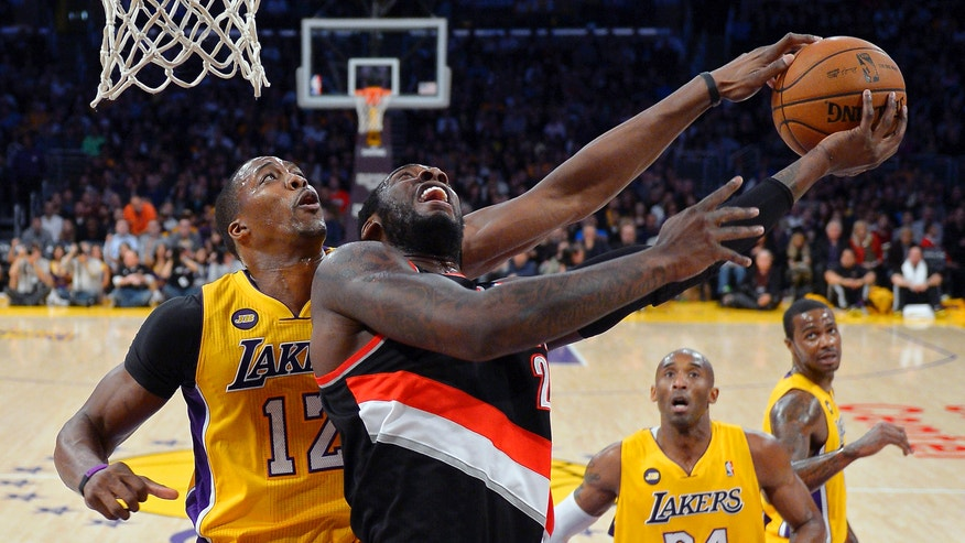 Los Angeles Lakers center Dwight Howard, left, blocks the shot of Portland Trail Blazers center J.J. Hickson as guard Kobe Bryant, second from right, and forward Earl Clark, right, look on during the first half of their NBA basketball game, Friday, Feb. 22, 2013, in Los Angeles. (AP Photo/Mark J. Terrill)