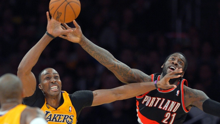 Los Angeles Lakers center Dwight Howard, left, and Portland Trail Blazers center J.J. Hickson go after a loose ball during the second half of their NBA basketball game, Friday, Feb. 22, 2013, in Los Angeles. The Lakers won 111-107. (AP Photo/Mark J. Terrill)