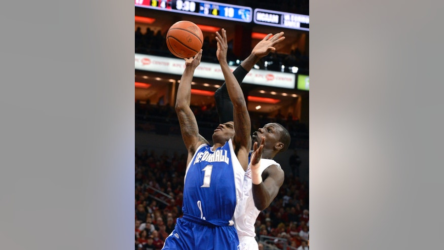 Seton Hall's Aaron Cosby (1) puts a shot up around the defense of Louisville's Gorgui Dieng during the first half of an NCAA college basketball game Saturday Feb. 23, 2013 in Louisville, Ky. (AP Photo/Timothy D. Easley)