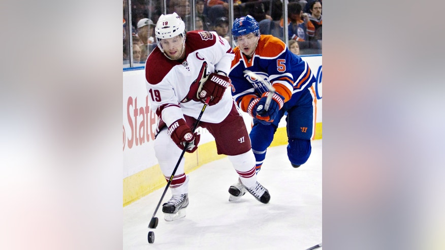 Phoenix Coyotes' Shane Doan (19) controls the puck as he is chased Edmonton Oilers' Ladislav Smid (5) during the first period of an NHL hockey game in Edmonton, Alberta, on Saturday, Feb. 23, 2013. (AP Photo/The Canadian Press, Jason Franson)