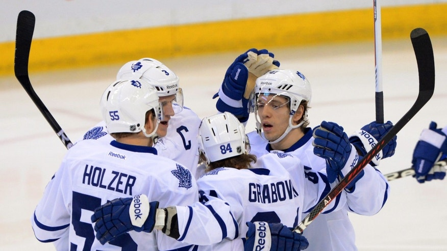 Toronto Maple Leafs' Mika Grabovski, second from right, celebrates his first-period goal against the Ottawa Senators with teammates Korbinian Holzer, left to right, Dion Phaneuf, and Nikolai Kulemin during an NHL hockey game in Ottawa, Ontario, on Saturday, Feb. 23, 2013. (AP Photo/The Canadian Press, Sean Kilpatrick)