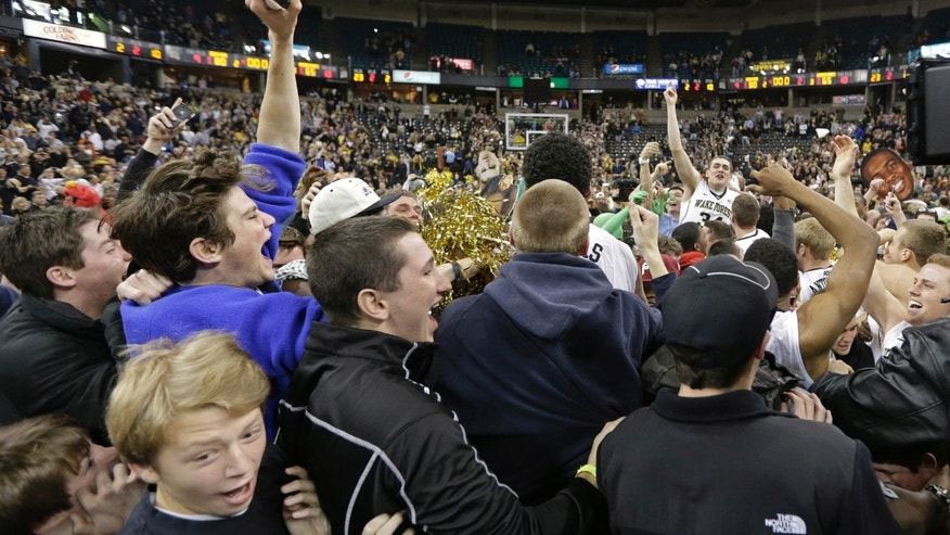 Wake Forest fans rush the court as they celebrate with players after their 80-65 win over No. 2 Miami in an NCAA college basketball game in Winston-Salem, N.C., Saturday, Feb. 23, 2013. (AP Photo/Chuck Burton)