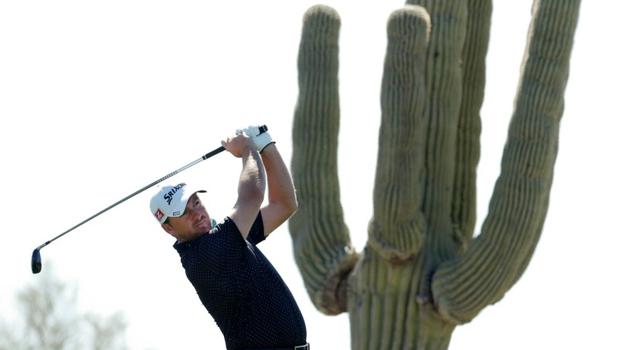Northern Ireland's Graeme McDowell tees off the fourth hole during the quarterfinal match against Jason Day at the Match Play Championship golf tournament, Saturday, Feb. 23, 2013, in Marana, Ariz. (AP Photo/Ross D. Franklin)