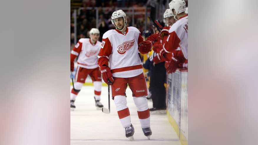 Detroit Red Wings left wing Drew Miller (20) is congratulated by teammates after scoring during the first period of an NHL hockey game against the Nashville Predators in Detroit, Saturday, Feb. 23, 2013. (AP Photo/Carlos Osorio)
