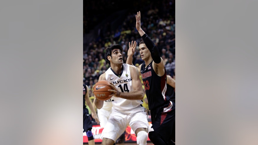 Oregon forward Arsalan Kazemi, left, from Iran, drives to the basket against Stanford forward Dwight Powell during the first half of an NCAA college basketball game in Eugene, Ore., Saturday, Feb. 23, 2013. (AP Photo/Don Ryan)