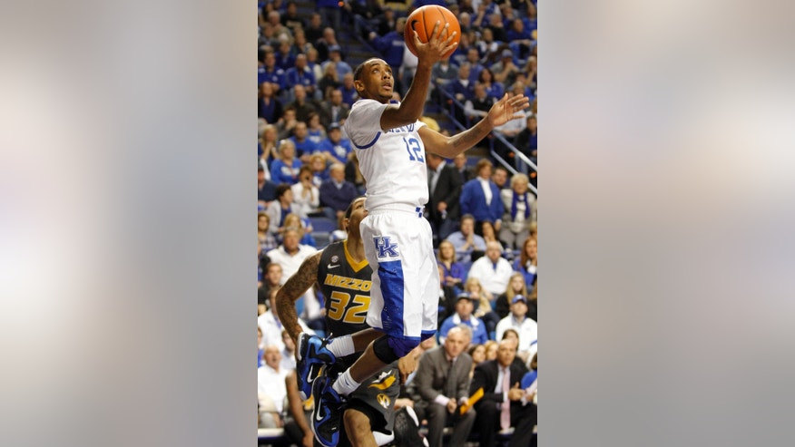 CORRECTS DAY OF WEEK - Kentucky's Ryan Harrow (12) shoots in front of Missouri's Jabari Brown during the first half of an NCAA college basketball game at Rupp Arena in Lexington, Ky., Saturday, Feb. 23, 2013. (AP Photo/James Crisp)