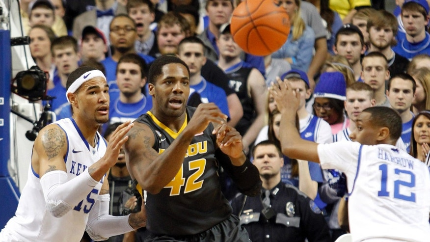 CORRECTS DAY OF WEEK - Missouri's Alex Oriakhi, center, has his pass deflected by Kentucky's Ryan Harrow (12) as Kentucky's Willie Cauley-Stein, left, watches during the first half of an NCAA college basketball game at Rupp Arena in Lexington, Ky., Saturday, Feb. 23, 2013. (AP Photo/James Crisp)