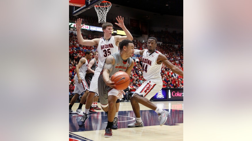 Washington State's DaVonte Lacy, center, looks to pass the ball as Arizona's Kaleb Tarczewski (35) and Solomon Hill (44) defend during the first half of an NCAA college basketball game at McKale Center in Tucson, Ariz., Saturday, Feb. 23, 2013. (AP Photo/Wily Low)