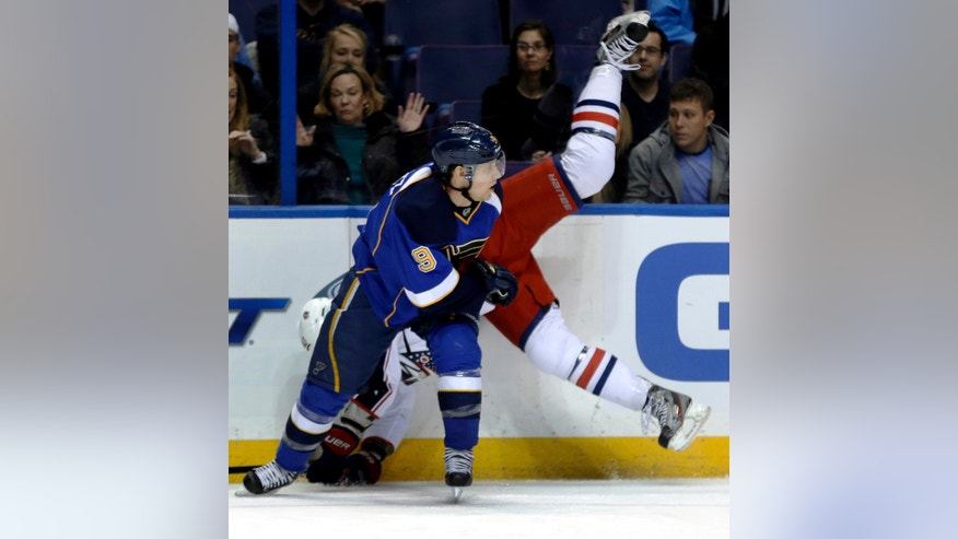 Columbus Blue Jackets' Jared Boll, rears slams into the boards while chasing a loose puck alongside St. Louis Blues' Jaden Schwartz during the first period of an NHL hockey game Saturday, Feb. 23, 2013, in St. Louis. (AP Photo/Jeff Roberson)