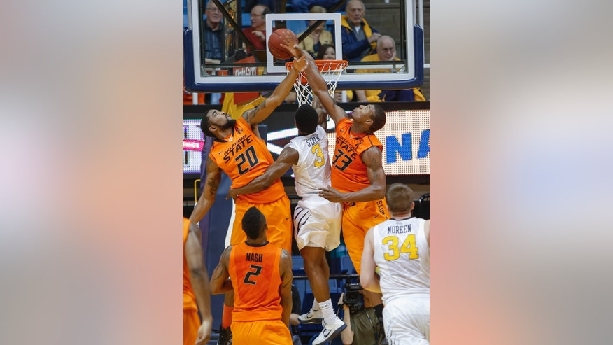 Oklahoma State's Marcus Smart (33) and Michael Cobbins (20) block the shot of West Virginia's Juwan Staten (3) during the second half of an NCAA college basketball game in Morgantown, W.Va., on Saturday, Feb. 23, 2013. Oklahoma State defeated West Virginia 73-57.(AP Photo/David Smith)