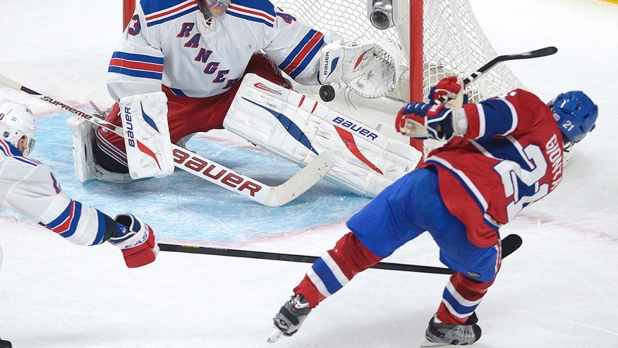 New York Rangers goaltender Martin Biron, left, makes a save against Montreal Canadiens' Brian Gionta during the second period  of an NHL hockey game in Montreal, Saturday, Feb. 23, 2013. (AP Photo/The Canadian Press, Graham Hughes)
