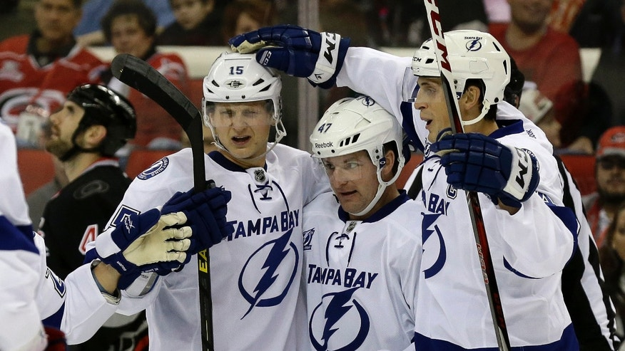 Tampa Bay Lightning's Brian Lee (15), Vincent Lecavalier, right, and Marc-Andre Bergeron (47) celebrate Bergeron's goal against the Carolina Hurricanes during the first period of an NHL hockey game in Raleigh, N.C., Saturday, Feb. 23, 2013. Tampa Bay won 5-2.  (AP Photo/Gerry Broome)