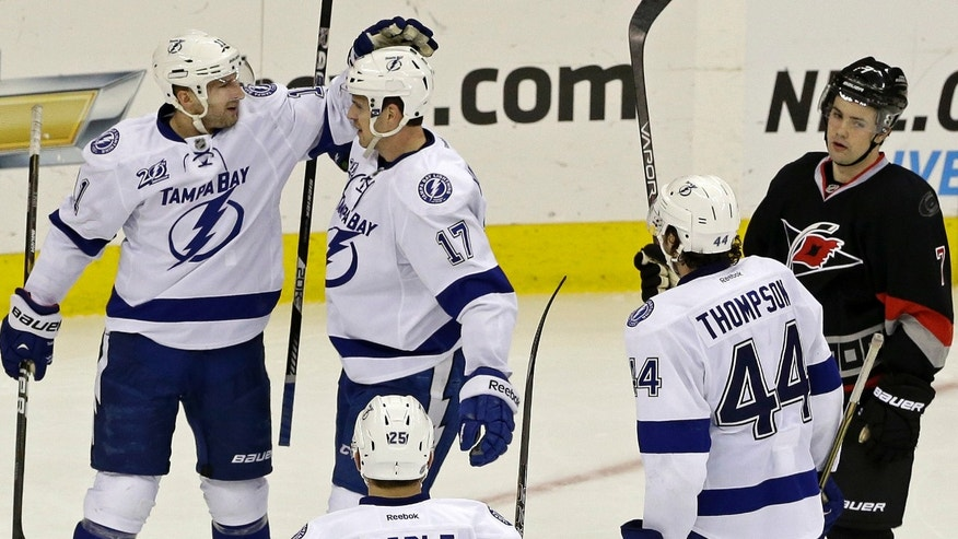 Tampa Bay Lightning's Tom Pyatt, left, celebrates his goal against the Carolina Hurricanes with Alex Killorn (17), Nate Thompson (44) and Matt Carle (25) as Hurricanes' Ryan Murphy (7) looks away at right during the third period of an NHL hockey game in Raleigh, N.C., Saturday, Feb. 23, 2013. Tampa by won 5-2. (AP Photo/Gerry Broome)