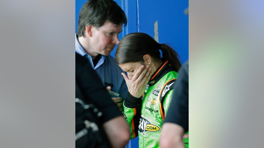 Danica Patrick, center, talks with members of her team in her garage after she had engine problems in the NASCAR Nationwide Series auto race at Daytona International Speedway, Saturday, Feb. 23, 2013, in Daytona Beach, Fla. (AP Photo/John Raoux)