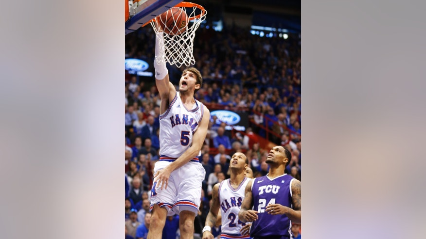 Kansas center Jeff Withey (5) dunks after getting past TCU forward Adrick McKinney (24) during the first half of an NCAA college basketball game in Lawrence, Kan., Saturday, Feb. 23, 2013. (AP Photo/Orlin Wagner)