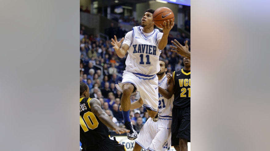 Xavier guard Dee Davis (11) drives against Virginia Commonwealth in the first half of an NCAA college basketball game, Saturday, Feb. 23, 2013, in Cincinnati. (AP Photo/Al Behrman)