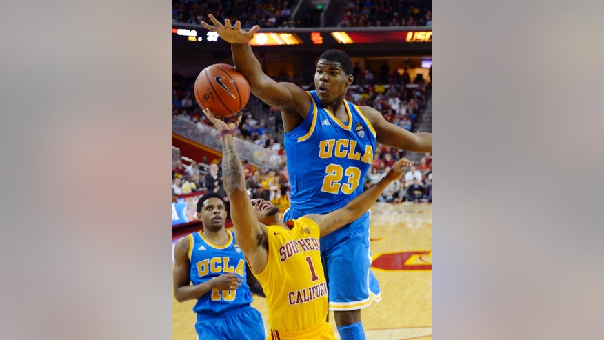 Southern California guard Jio Fontan (1) shoots as UCLA forward Tony Parker (23) defends and guard Larry Drew II watches during the first half of their NCAA college basketball game, Sunday, Feb. 24, 2013, in Los Angeles. (AP Photo/Mark J. Terrill)