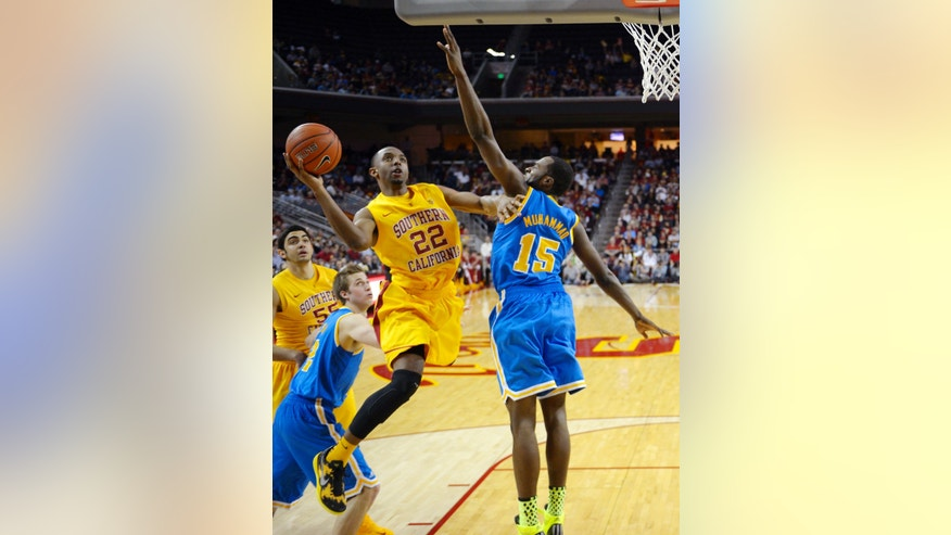 Southern California guard Byron Wesley (22) shoots as UCLA's Shabazz Muhammad (15) defends during the first half of their NCAA college basketball game, Sunday, Feb. 24, 2013, in Los Angeles. (AP Photo/Mark J. Terrill)