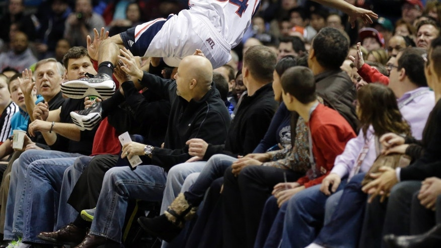 Atlanta Hawks' Devin Harris flips over fans trying to save the ball against the Milwaukee Bucks during the first half of an NBA basketball game, Saturday, Feb. 23, 2013, in Milwaukee. (AP Photo/Jeffrey Phelps)
