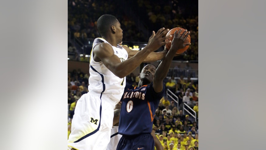 Michigan forward Glenn Robinson III (1) and Illinois forward Sam McLaurin (0) battle for the rebound during the first half of an NCAA college basketball game, Sunday, Feb. 24, 2013 in Ann Arbor, Mich. (AP Photo/Carlos Osorio)