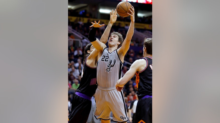 San Antonio Spurs' Tiago Splitter (22), of Brazil, shoots next to Phoenix Suns' Luis Scola, left, of Argentina, during the first half of an NBA basketball game, Sunday, Feb. 24, 2013, in Phoenix. (AP Photo/Matt York)