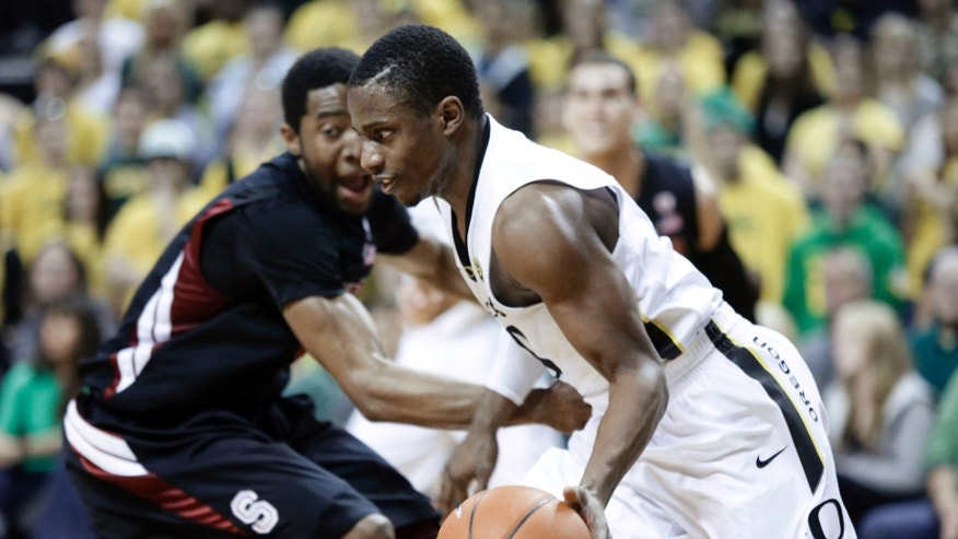 Oregon guard Johnathan Loyd, right, drives on Stanford guard Chasson Randle during the second half of an NCAA college basketball game in Eugene, Ore., Saturday, Feb. 23, 2013. Loyd scored 15 points as Oregon won 77-66. (AP Photo/Don Ryan)