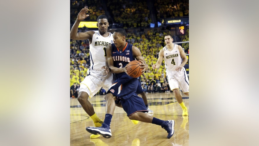 Illinois guard Joseph Bertrand (2) drives to the basket while defended by Michigan forward Glenn Robinson III (1) during the first half of an NCAA college basketball game, Sunday, Feb. 24, 2013 in Ann Arbor, Mich. (AP Photo/Carlos Osorio)