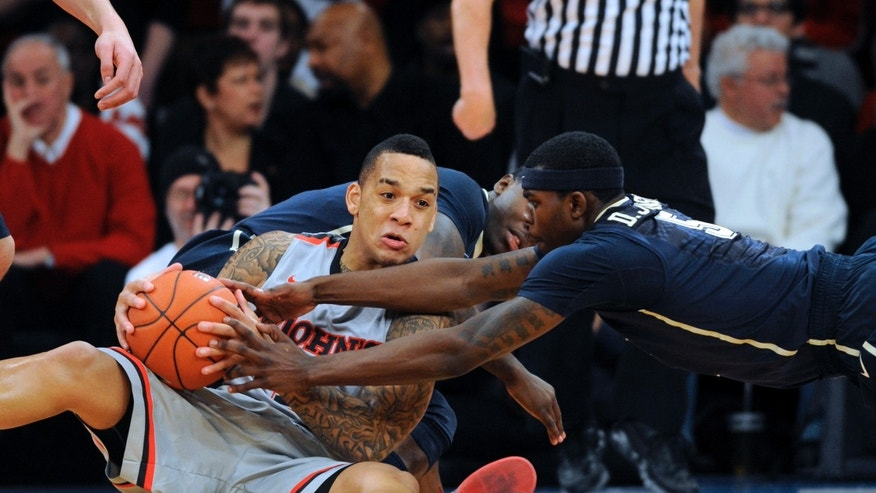 St. John's D'Angelo Harrison, left, fights for a loose ball with Pittsburgh's Durand Johnson in the first half of the NCAA college basketball game at Madison Square Garden in New York, Sunday, Feb. 24, 2013. (AP Photo/Henny Ray Abrams)