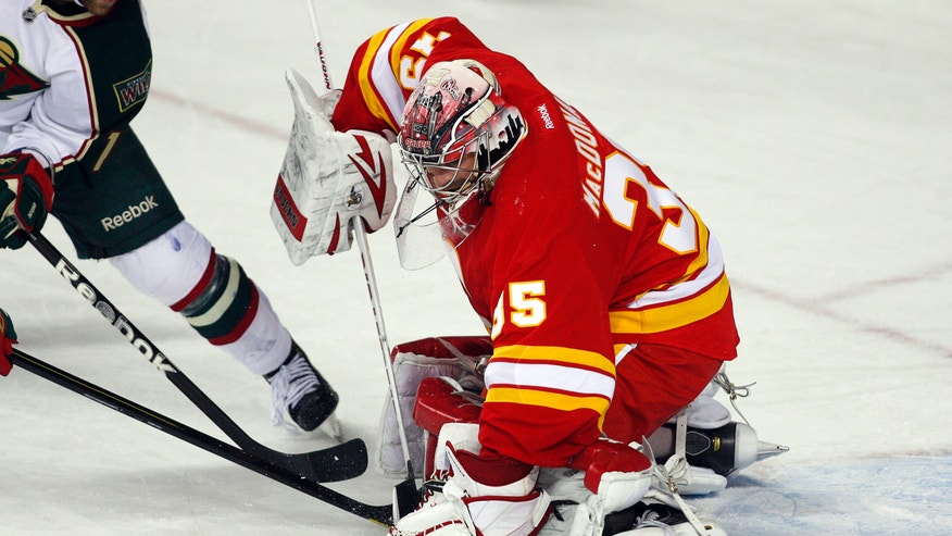 Minnesota Wild's Jason Zucker, left, tries to get the puck past Calgary Flames goalie Joey MacDonald during the second period of an NHL hockey game in Calgary, Alberta, Saturday, Feb. 23, 2013. (AP Photo/The Canadian Press, Jeff McIntosh)