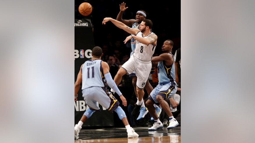 Brooklyn Nets' Deron Williams, center, passes through Memphis Grizzlies defense during the first half of the NBA basketball game at the Barclays Center Sunday, Feb. 24, 2013 in New York.  (AP Photo/Seth Wenig)