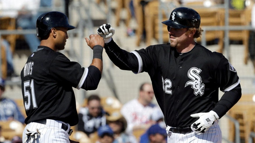 Chicago White Sox's Adam Dunn, right, is congratulated by Alex Rios (51) after hitting a two-run home run against the Los Angeles Dodgers in the fourth inning of an exhibition spring training baseball game in Glendale, Ariz., Sunday, Feb. 24, 2013. (AP Photo/Paul Sancya)