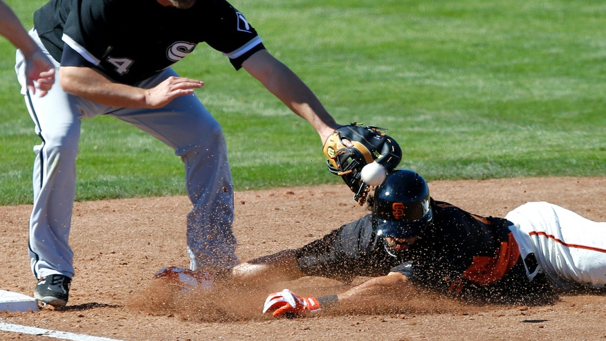 Chicago White Sox first baseman Paul Konerko, left, can't make the catch as San Francisco Giants' Angel Pagan dives back to first during the second inning of a spring training baseball game, Monday, Feb. 25, 2013, in Scottsdale, Ariz. (AP Photo/Matt York)