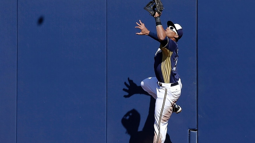 Milwaukee Brewers' Carlos Gomez goes up the wall to get a ball hit by San Diego Padres' Nick Hundley during the second inning of an exhibition spring training baseball game Monday, Feb. 25, 2013, in Phoenix. (AP Photo/Morry Gash)