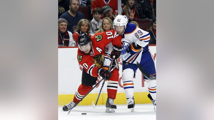 Chicago Blackhawks center Patrick Sharp (10) battles Edmonton Oilers center Sam Gagner (89) for a loose puck during the first period of an NHL hockey game, Monday, Feb. 25, 2013, in Chicago. (AP Photo/Charles Rex Arbogast)