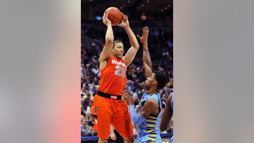 Syracuse's Brandon Triche (20) looks to pass over Marquette's Vander Blue during the second half of an NCAA college basketball game, Monday, Feb. 25, 2013, in Milwaukee. (AP Photo/Jim Prisching)