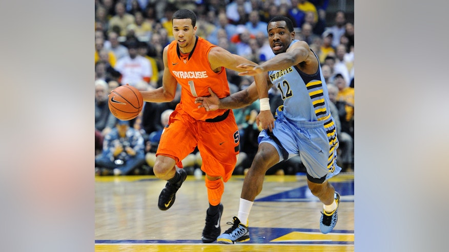 Syracuse's Michael Carter-Williams (1) dribbles past Marquette's Derrick Wilson (12) during the second half of an NCAA college basketball game, Monday, Feb. 25, 2013, in Milwaukee. (AP Photo/Jim Prisching)